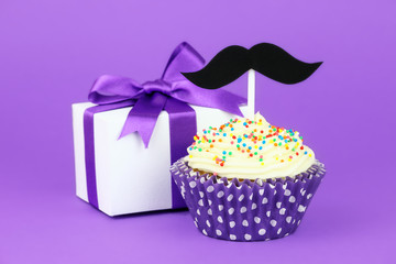 Happy Father's Day greeting with gift and a cupcake on purple
