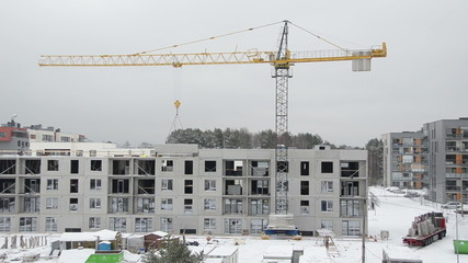 Crane lift house part and builders workers work in winter