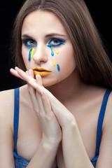 Girl crying yellow blue tears.