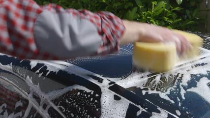Car Care - Man washing a car by hand using a sponge