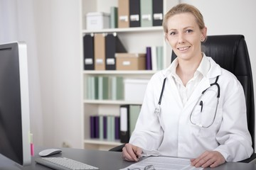 Female Physician at her Desk Looking at Camera