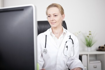 Woman Doctor at her Office Facing Computer Monitor