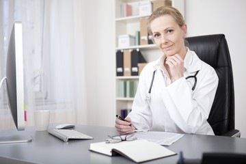 Female Doctor at her Table with Pen and Paper