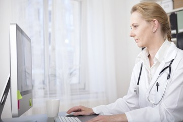 Female Doctor at her Desk Using her Computer