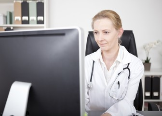 Woman Doctor Looking at Computer Monitor Seriously