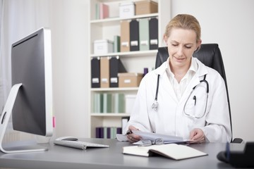 Physician Reviewing her Written Findings on Paper