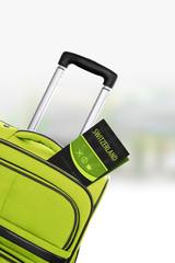 Switzerland. Green suitcase with guidebook.