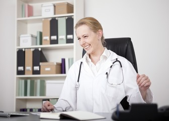 Happy Female Medical Doctor Sitting at her Office