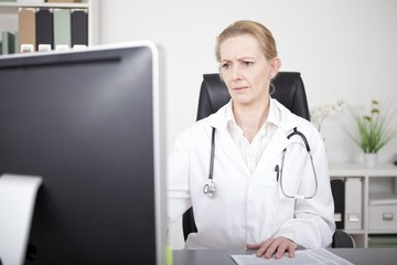 Serious Female Doctor Looking at Computer Monitor
