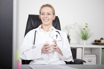Happy Doctor on her Chair with a Cup of Coffee