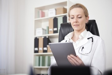Adult Female Doctor Looking at her Tablet Screen