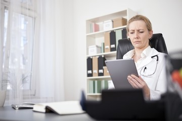 Serious Medical Doctor Reading at her Tablet