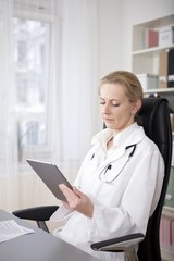Pensive Female Doctor Looking at Tablet Screen