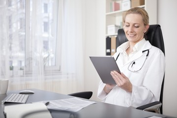 Happy Woman Physician Using her Tablet Device