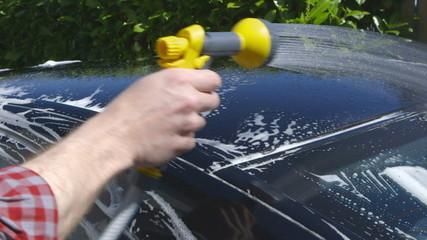 Car Care - Man using a garden spray gun