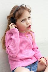 singing little girl wearing headphones