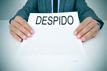 businessman shows a document with the text despido, dissmissal i