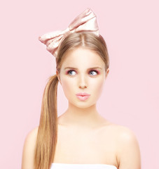 Beautiful young girl with a big pink bow in her hair