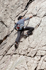 Young woman climbing difficult wall.