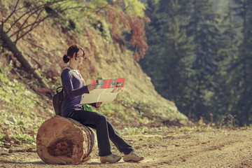 Young lady reading travel map during hike