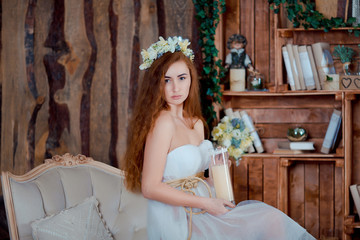 Beautiful rude girl with candle in wood interior