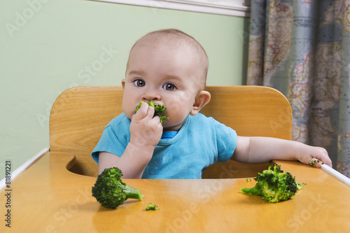 Poster Cute baby eating broccoli