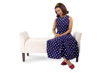 woman wearing a blue polka dot dress looking at something
