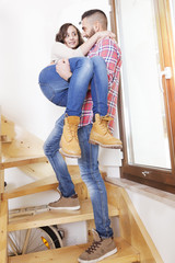 young man holding his girlfriend in his arms after moving