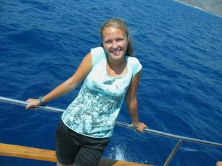 Счастливая девушка на яхте улыбается солнцу и ветру