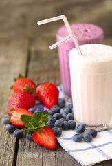 milk shakes and fresh berries on a dark wooden background