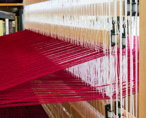 A loom set up with red wool warp threads ready for weaving