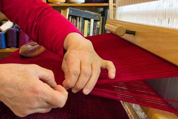 Weaver Adjusts Edge of Fabric She is Weaving