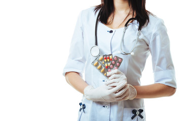 Young and friendly woman doctor holding offering pills isolated