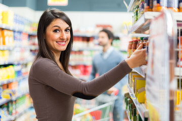 Woman taking a product in a supermarket