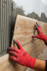 Ceramic Tiles. Tiler placing ceramic wall tile in position over