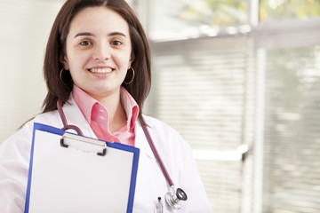 Portrait of a friendly female doctor holding a medical clipboard