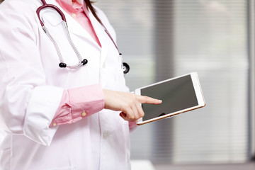 Female doctor working with digital tablet at the office