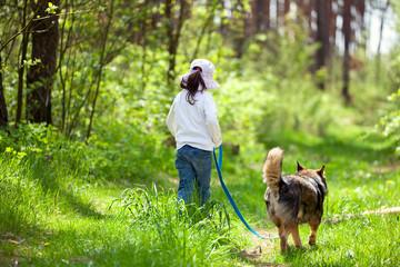 Little girl walking with dog