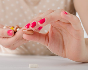 Young Woman hand holding  pills.