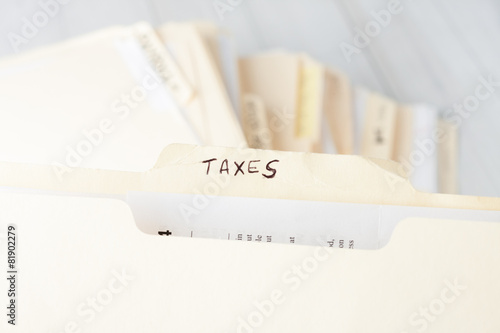 yellow paper folder labeled TAXES - 81902279