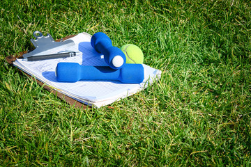 Exercise equipment, tennis ball, and clipboard on grass