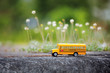 Yellow school bus toy model on country road. - 81903694