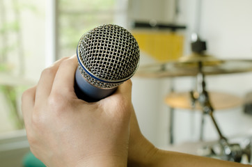 Hands holding a microphone in music room