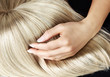 Straight blond wig brushing by a woman - 81904626