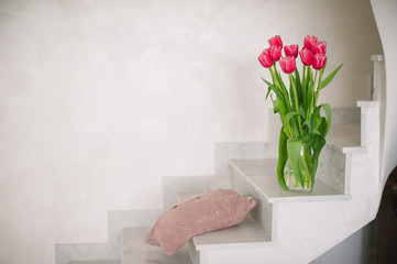 Bouquet of pink tulips in a vase on the white marble steps