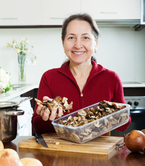 Happy mature woman with dried mushrooms