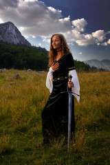 mystical woman with sword and historic dress on mountain meadow