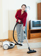 Happy mature woman with vacuum cleaner