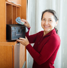 Happy mature woman wiping dust