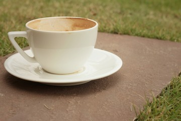 White coffee cup with saucer on the lawn.